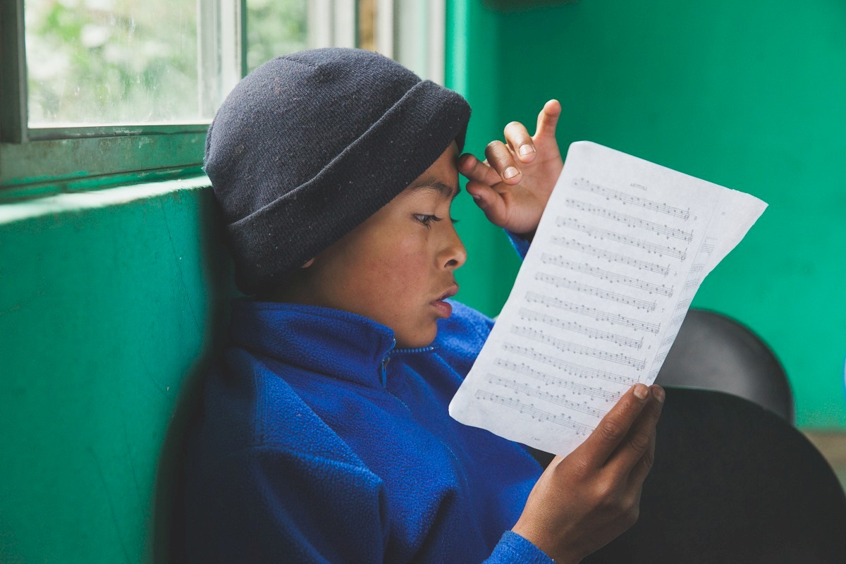 A music student studies his notes. Mixe people have a long musical tradition whose legacy is continued through the efforts of students who later become teachers, travelling the region to maintain a structured learning system.