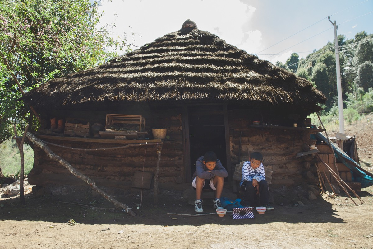 Two brothers watch cartoons on a tablet in front of a traditional house in the mountains of Oaxaca. While there is almost no cellular service or internet in most of the region, people find ways to get a dosage of technology.