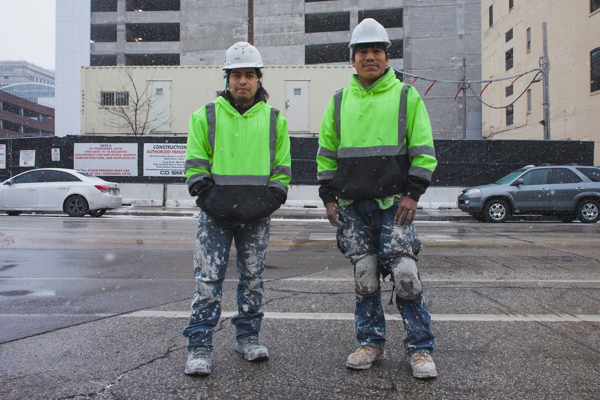 Two construction workers finishing their shifts as snow begins to fall.