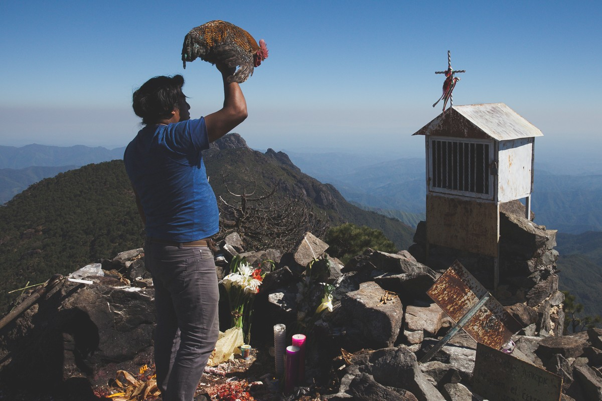 On top of Cempoaltépetl, the highest peak in the Sierra Mixe mountain range and a sacred location, Timio performs pre-hispanic rituals to ask for spiritual help for his brother who has immigrated away from home.