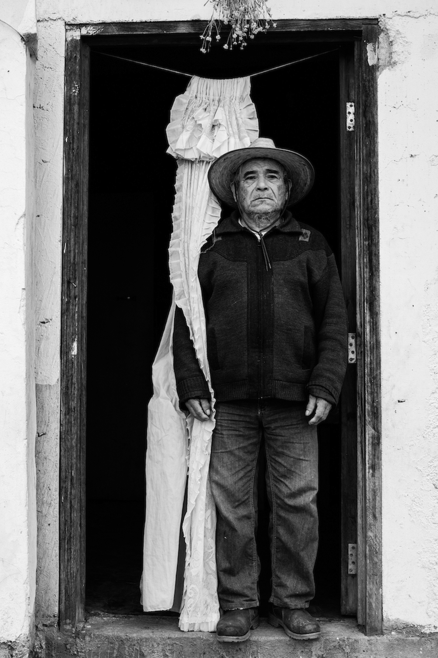 A Mixe man poses in his front door. Tamazulapam del Espiritu Santo, Oaxaca, Mexico.