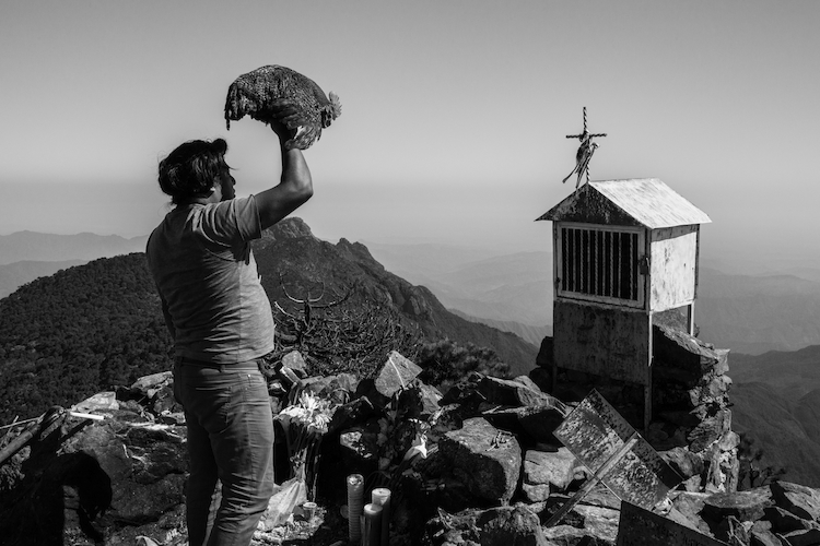 A Mixe man performs pre-hispanic rituals to send spiritual help to his brother who has migrated north. Tamazulapam del Espiritu Santo, Oaxaca, Mexico.