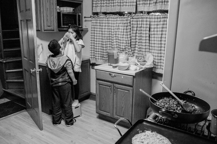 Mixe children hanging out in the kitchen with typical Mexican food on the stove. Milwaukee, Wisconsin, USA.