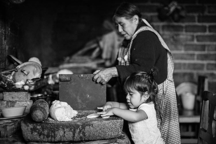 A grandmother passes on tortilla technique to her granddaughter. Tamazulapam del Espiritu Santo, Oaxaca, Mexico.